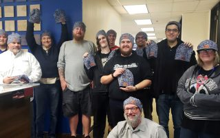Guida Surveying Bay Area staff holding holiday beanies for donation